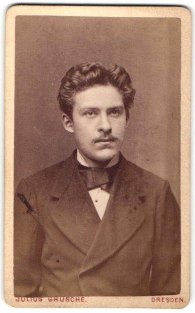 Fotografie Julius Grusche, Dresden, Portrait hübscher dunkelhaariger Mann mit Oberlippenbart und Fliege