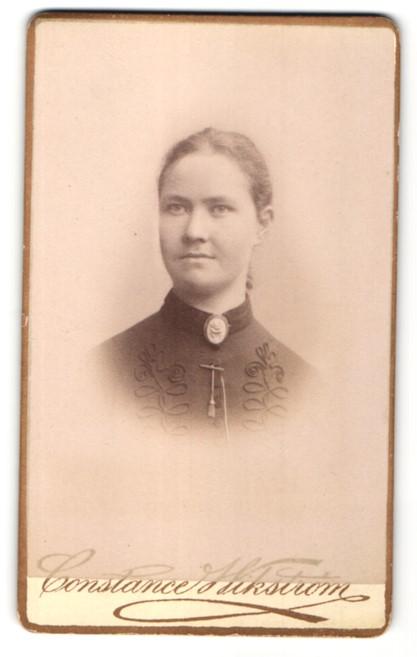 Fotografie Constance Wikström, Norrköping, Portrait hübsche junge Frau mit Brosche und elegant bestickter Bluse
