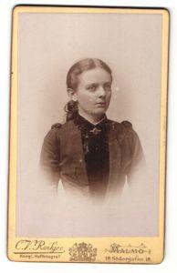 Fotografie C. V. Roikjer, Malmö, freundliche junge Dame mit zurückgebundenem Haar und Brosche am Kragen