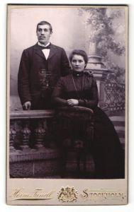 Fotografie Herm. Tunell, Stockholm, Portrait traumhaft schönes Paar in eleganter dunkler Kleidung