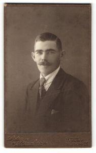 Fotografie Atelier Bruzelius, Wisby, Portrait charmanter dunkelhaariger Mann mit Schnurrbart