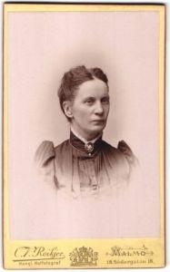 Fotografie C. V. Roikjer, Malmö, Portrait schöne Frau mit zurückgebundenem Haar und Brosche am Kragen