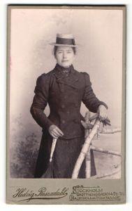 Fotografie Hedvig Rosendahl, Stockholm, Portrait charmante Dame mit Hut und Handschuhen im Mantel