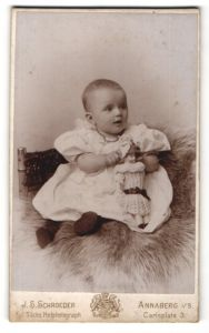 Fotografie J. S. Schroeder, Annaberg i/S, Portrait Säugling mit Puppe