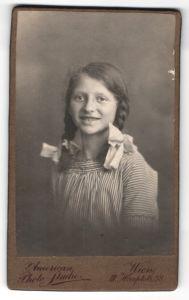 Fotografie American Photo-Studio, Wien, Portrait lachendes Mädchen mit Flechtzöpfen und Haarschleifen