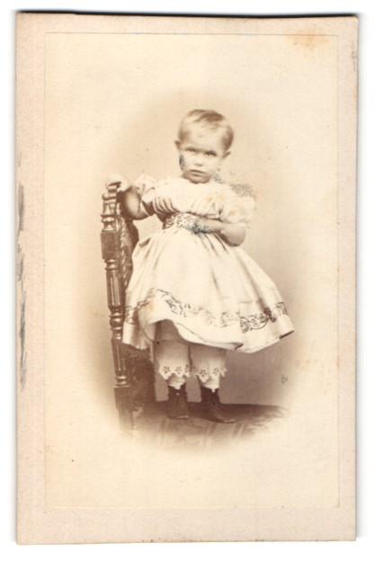 Fotografie Fotograf unbekannt, Ort unbekannt, kleines Mädchen in Kleid mit Unterhosen