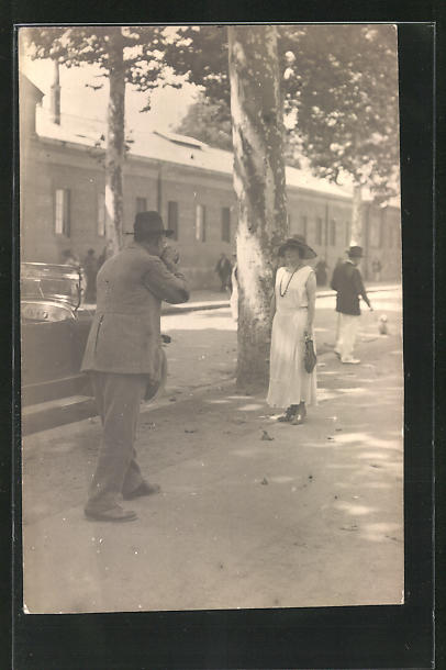 AK Fotoapparat, Mann fotografiert Frau im weissen Kleid mit Hut
