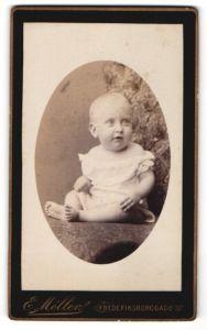 Fotografie E. Möller, Kjöbenhavn, Portrait niedliches blondes Kleinkind im weissen Kleidchen mit Rüschen