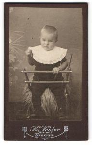 Fotografie K. Vester, Grenaa, Portrait niedliches blondes Kleinkind im Kinderstuhl