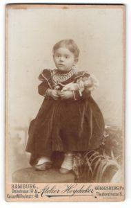 Fotografie Atelier Heydecker, Hamburg, Portrait niedliches kleines Mädchen mit Puppe im Arm