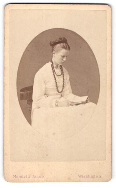 Fotografie Mondel & Jacob, Wiesbaden, Portrait junge hübsche Dame mit Halskette und Buch auf einem Stuhl sitzend