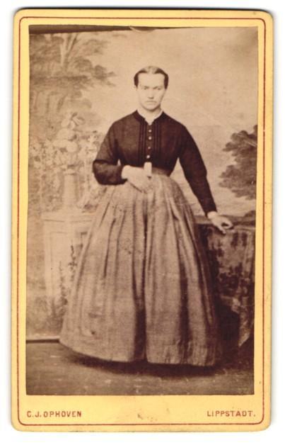 Fotografie C. J. Ophoven, Lippstadt, Portrait junge Dame mit Mittelscheitel an einem Tisch lehnend