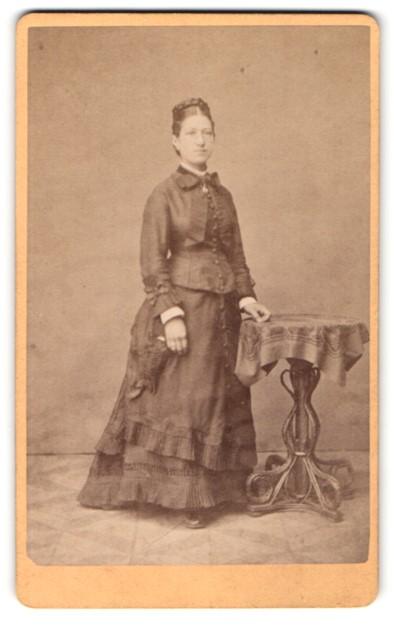 Fotografie J. Freund, Schlüchtern, Portrait bürgerliche Dame mit Flechtfrisur am Tisch lehnend