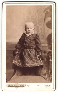 Fotografie H. Schmiedehausen, Wien, Portrait Kleinkind im karierten Kleidchen auf einem Sessel stehend
