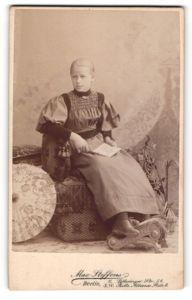 Fotografie Max Steffens, Berlin, Portrait Mädchen in festlicher Kleidung auf Sitzmöbel
