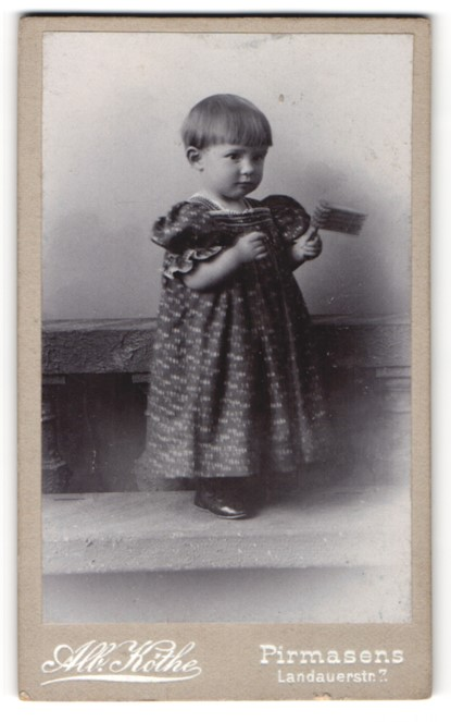Fotografie Alb. Köthe, Pirmasens, Portrait kleines Mädchen mit Ratsche, Spielzeug