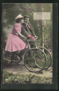 AK Frau mit Mütze auf Fahrrad umarmt Mann auf Fahrrad