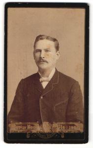 Fotografie Gustav Mook, Giessen, Portrait bürgerlicher Herr mit Schnurrbart und Fliege im Anzug