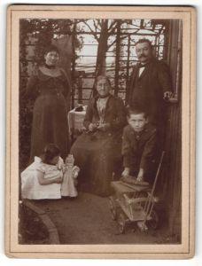 Fotografie unbekannter Fotograf und Ort, Portrait Familie mit Kindern mit Spielzeug, Puppe, Bollerwagen