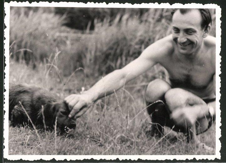 Fotografie Mann in Badehose ärgert Hund - Dackel