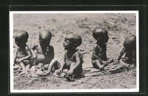 AK Afrikanische nackte Kleinkinder sitzen weinend in der Steppe, afrikanische Volkstypen