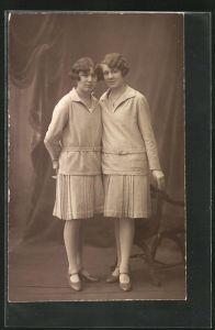 Foto-AK Portrait junger Damen als Zwillinge in gleicher Kleidung in einer Studiokulisse