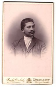 Fotografie Arnold Overbeck, Düsseldorf, Portrait junger Herr mit Zwirbelbart und Krawatte im Anzug