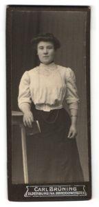Fotografie Carl Brüning, Oldenburg i / Gr., Portrait junge lächelnde Dame in weisser Bluse mit Buch an Tisch gelehnt