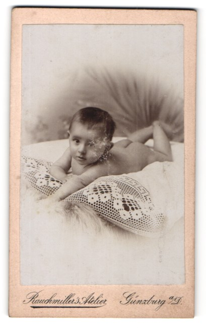 Fotografie Raumiller`s Atelier, Günzburg a / D., Portrait Kleinkind auf einem Kissen liegend