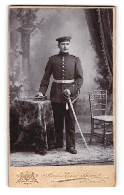 Fotografie Atelier Carl Beste, Minden i / W., Portrait Soldat in Uniform mit Schirmmütze und Degen an Tisch gelehnt