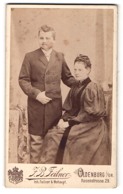 Fotografie J. B. Feilner, Oldenburg i / Gr., Portrait ältere bürgerliche Dame mit Haube auf Stuhl sitzend und Herr
