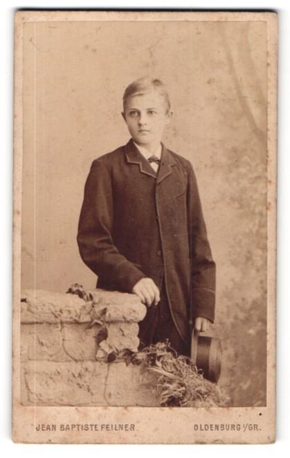 Fotografie Jean Baptiste Feilner, Oldenburg i / Gr., Portrait hübscher Knabe im Mantel mit Hut an Sockel gelehnt