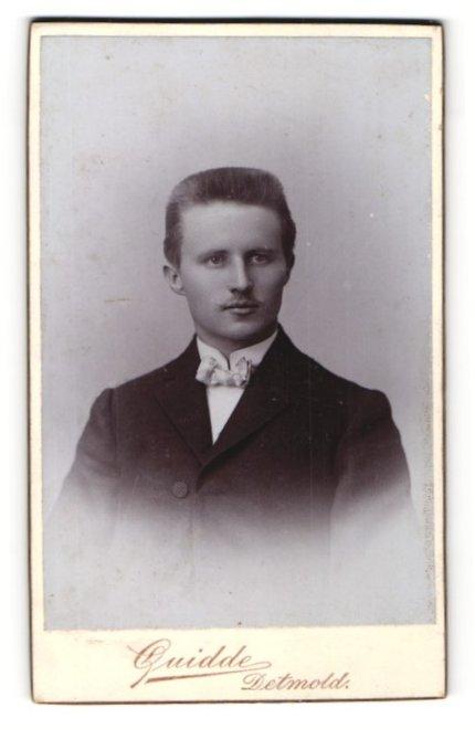 Fotografie Guidde, Detmold, Portrait charmanter junger Herr mit Oberlippenbart und Fliege im Anzug