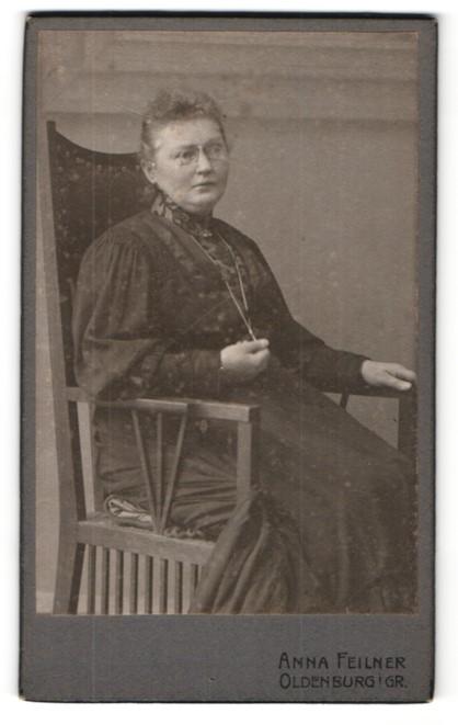 Fotografie Anna Feilner, Oldenburg i / Gr., Portrait ältere Dame mit Brille in zeitgenössischem Kleid auf Stuhl sitzend