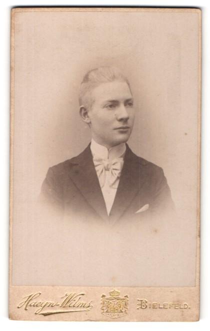 Fotografie Haeyn-Wilms, Bielefeld, Portrait junger charmanter Herr mit Fliege im Anzug