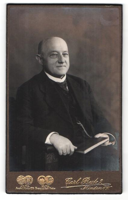 Fotografie Carl Beste, Minden i / W., Portrait älterer Herr mit Buch auf Stuhl sitzend im Anzug