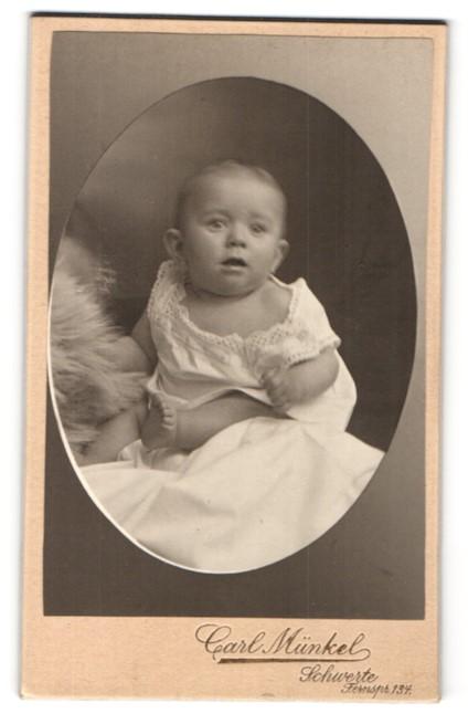 Fotografie Carl Münkel, Schwerte, Portrait niedliches Baby im weissen Hemd mit Fell auf Laken sitzend