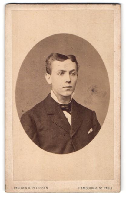 Fotografie Paulsen & Petersen, Hamburg & St. Pauli, Portrait junger charmanter Herr mit Fliege im Anzug