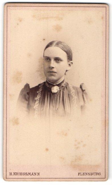 Fotografie H. Kriegsmann, Flensburg, Schöne junge Frau mit Brosche am Kragen