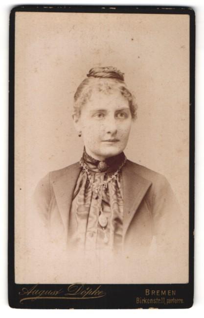 Fotografie August Döpke, Bremen, Portrait lächelnde Dame mit Hochsteckfrisur und Halskette in modischer Kleidung