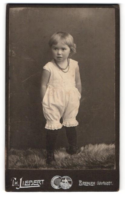 Fotografie Th. Liebert, Bremen, Portrait kleines Mädchen mit Halskette in weissen Hosen mit Händen in den Taschen