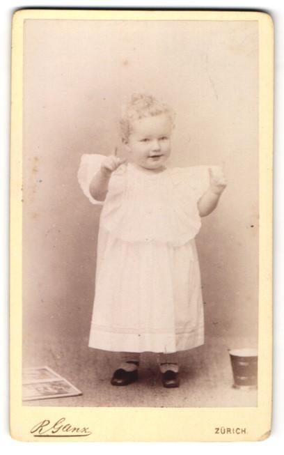 Fotografie R. Ganz, Zürich, Portrait kleines lächelndes Mädchen im weissen Kleid