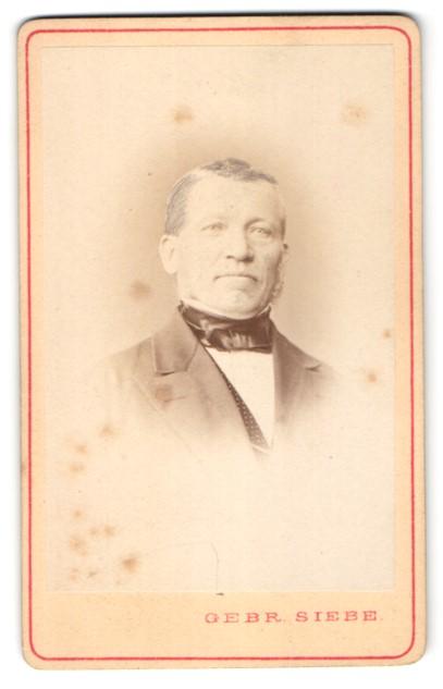 Fotografie Gebr. Siebe, Breslau, Stettin, Leipzig, Portrait älterer Herr mit Fliege im Anzug