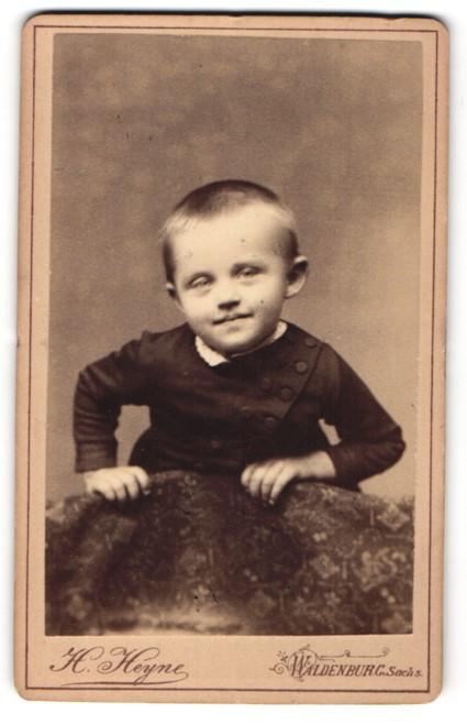 Fotografie H. Heyne, Waldenburg / Sachs., Portrait kleines Mädchen in modischer Kleidung auf eine Lehne gestützt