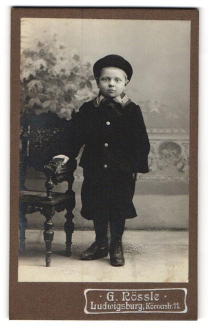 Fotografie G. Rössle, Ludwigsburg, Portrait kleiner Junge mit Hut im Anzug an Stuhl gelehnt