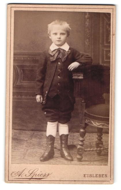 Fotografie A. Spiess, Eisleben, Portrait kleiner Junge im Anzug an Stuhl gelehnt