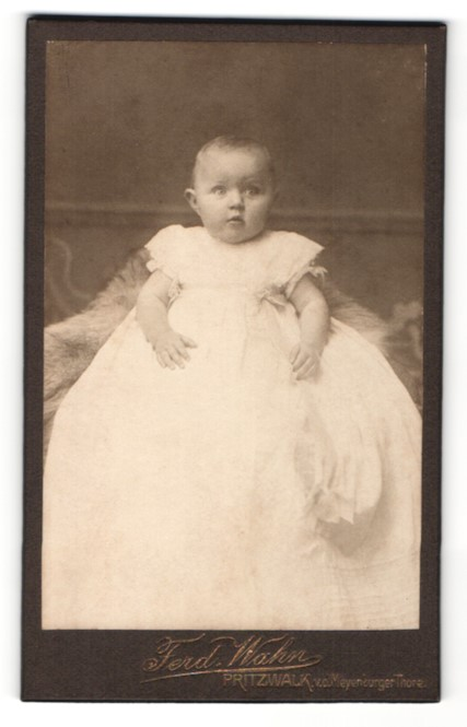 Fotografie Ferd. Wahn, Pritzwalk, Portrait niedliches Baby im weissen Kleid auf Fell sitzend