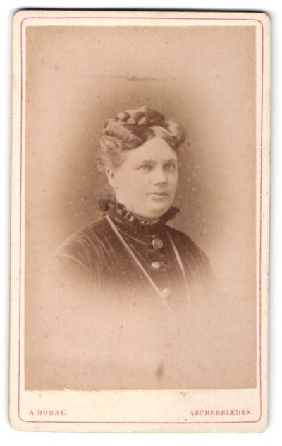 Fotografie A. Bohne, Aschersleben, Portrait lächelnde Dame mit Flechtfrisur in zeitgenössischer Kleidung