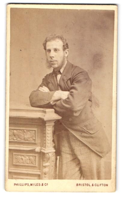 Fotografie Phillips, Miles & Co., Bristol & Clifton, Portrait bürgerlicher Herr mit Backenbart auf einem Sockel lehnend