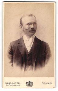 Fotografie Gebr. Lützel, München, Portrait bürgerlicher Herr mit Zwicker u. Schnauzbart im Anzug